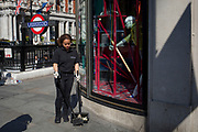 A female member of the Harvey Nichols In Store Services sweeps litter on the corner of Knightsbridge and Sloane Street, on 11th April 2019, in London, England.