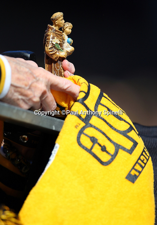 A Pittsburgh Steelers fan holds a religious statue and a terrible towel during the NFL football game against the Minnesota Vikings, October 25, 2009 in Pittsburgh, Pennsylvania. The Steelers won the game 27-17. (©Paul Anthony Spinelli)