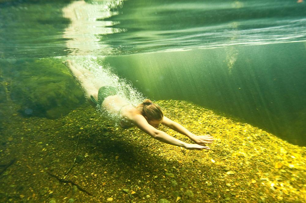 Plongeuse perce la surface de l'eau d'une rivière de Adirondak. | Diver enter water of an Adirondak river.