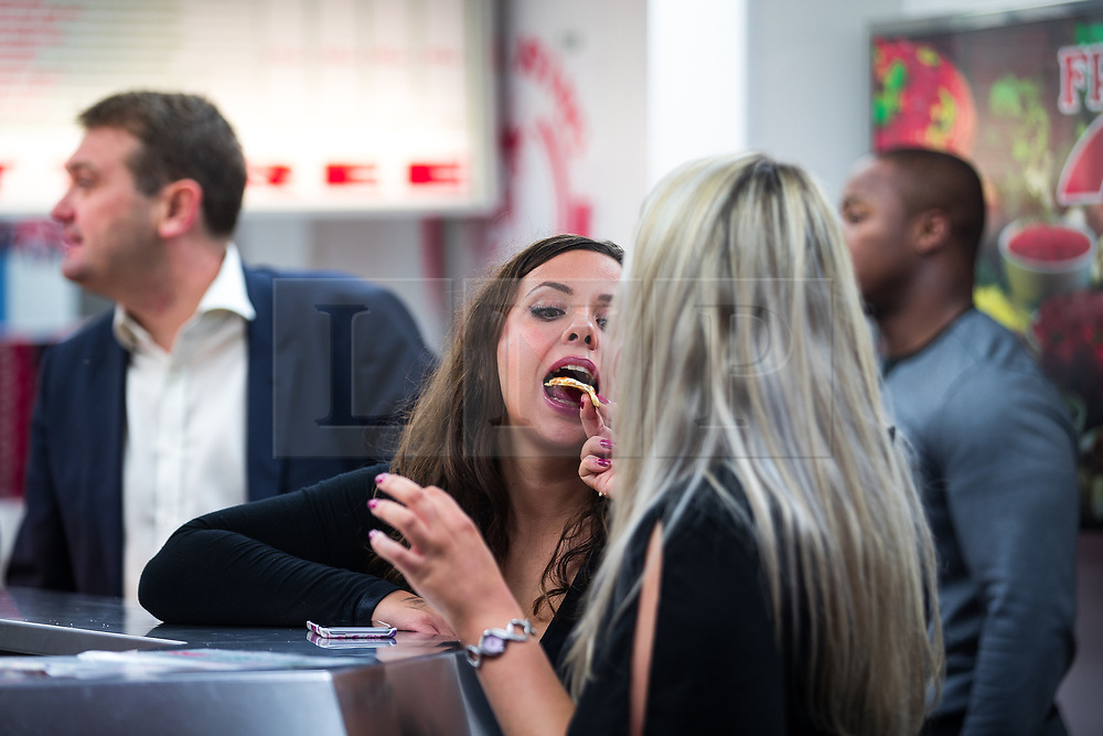 © Licensed to London News Pictures . 26/09/2017. Brighton, UK. A woman feeds another a slice of pizza . Revellers at the end of a night out on Brighton Promenade during Freshers week , when university students traditionally enjoy the bars and clubs during their first nights out in a new city . Photo credit: Joel Goodman/LNP