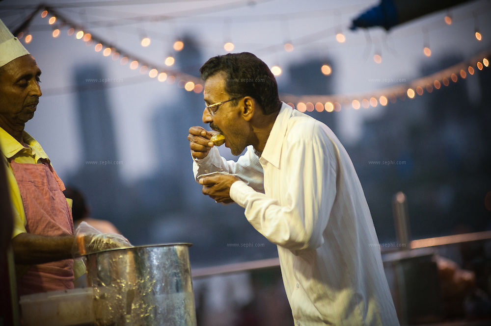 A man visiting chowpati beach just after sunset, enjoys Pani Puri, as the vendor looks on. Mumbai. August 2009