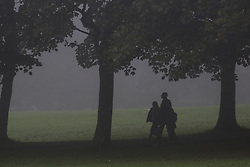 © Licensed to London News Pictures. 15/07/2016. Leeds, UK. A family walk through Hyde Park on a foggy autumn morning in Leeds, West Yorkshire. The start of the month has seen temperatures reach the highest they have been in the UK during September since 1911. Photo credit : Ian Hinchliffe/LNP