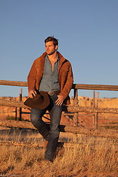 cowboy leaning on a fence at sunset