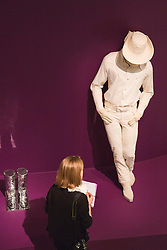 "© Licensed to London News Pictures. 21/10/2013. London, England. A visitor stands in front of the figure of a large white cowboy. The Exhibition ""Pop Art Design"" opens at the Barbican Art Gallery/Barbican Centre running from 22 October 2013 to 9 February 2014. The exhibition brings together 200 works by 70 artists and designers including Peter Blake, Andy Warhol and Roy Lichtenstein. Photo credit: Bettina Strenske/LNP"