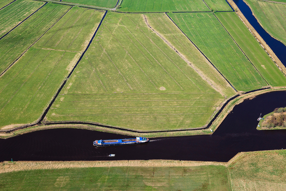 Nederland, Friesland, gemeente Tietjerksteradeel, 01-05-2013; binnenvaartschip op binnenwater op het Friese platteland, ten westen van Drachten.<br /> Barge on the inland water in the northern Netherlands. <br /> luchtfoto (toeslag op standard tarieven)<br /> aerial photo (additional fee required)<br /> copyright foto/photo Siebe Swart