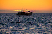 Celestun, Mexico -Jan 17 : orange and blue sun set and the silhouette of a fishing boat anchored at sea on 17 Jan at Celestun, Gulf of Mexico