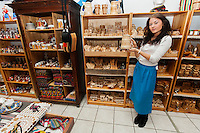 Full length of young woman displaying product in gift store