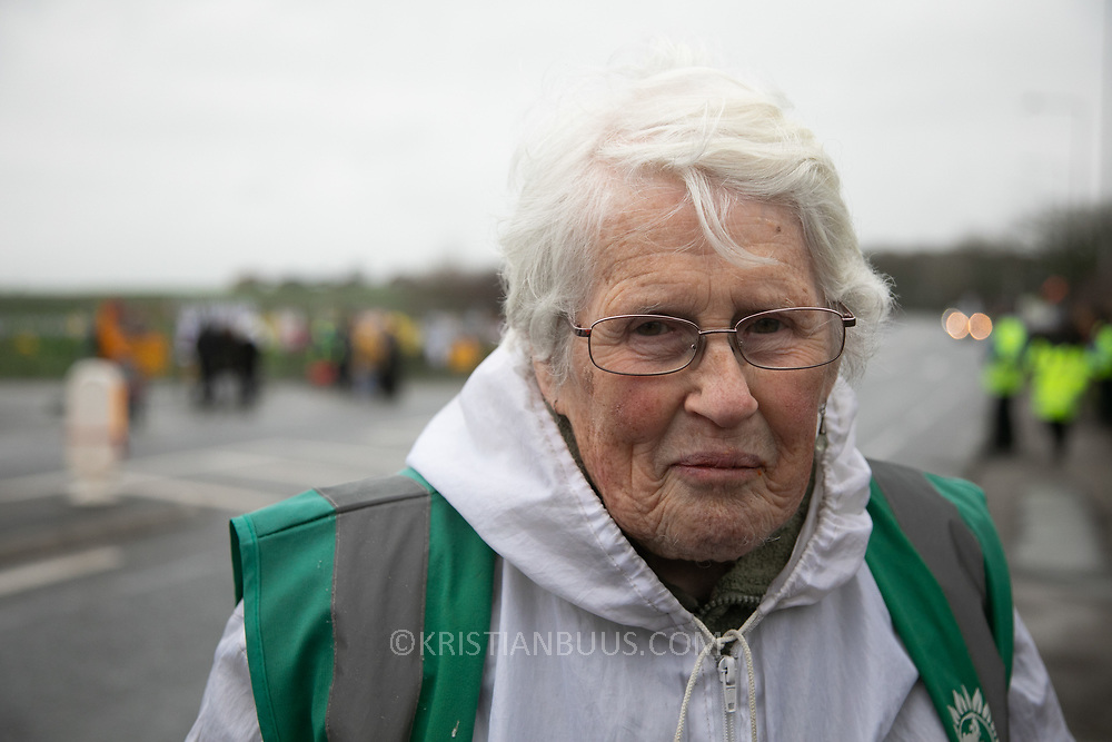 """Anne Power.<br /> """"I am Anne Power, I love my second name and I have just had my 87th birthday. What is going on here is a bit mysterious, my sense is the tide is turning, this site here which has been trying desperately hard to frack, causing earth quakes, is closing down, or something big is changing. Lots of equipment has gone, there is no tower which is a huge symbol."""" It is Green Monday and first week of the second anniversary of Cuadrilla's fracking exploration in Preston New Road. For two years activists have been keeping an eye on the fracking company Cuadrilla from the roadside of the fracking site in Preston New Road. The company has not actively fracked since November and is currently seemingly busy emptiyng the site for heavy equipment. Prostesters and climate protectors are still by the gates trying to work out Cuadrilla's intensions."""