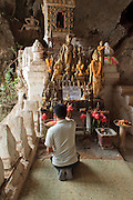 Mar. 14, 2009 -- LUANG PRABANG, LAOS: A man prays at a Buddhist shrine in the Pak Ou caves near Luang Prabang. The caves house thousands of Buddha statues and is one of the most important Buddhist sites in Laos. Photo by Jack Kurtz