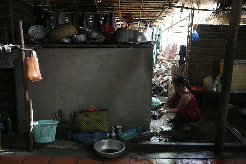 Cai Be, a village on a bank of the first arm (Tien Gang) of the Mekong River, Vietnam. .March 18th 2007..A woman washes dishes..