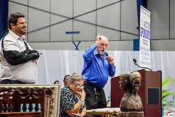 Auctioneers Leigh Goldman, left, and George Blackhall take bids on auction items.  The Hebrew Congregation of St. Thomas presents its seventeenth annual Antiques, Art & Collectibles at Antilles' MCM Center.  The annual silent and live auction supports upkeep and maintenance of the Historic Synangogue and its community programs.   St. Thomas, USVI.  21 February 2016.  © Aisha-Zakiya Boyd