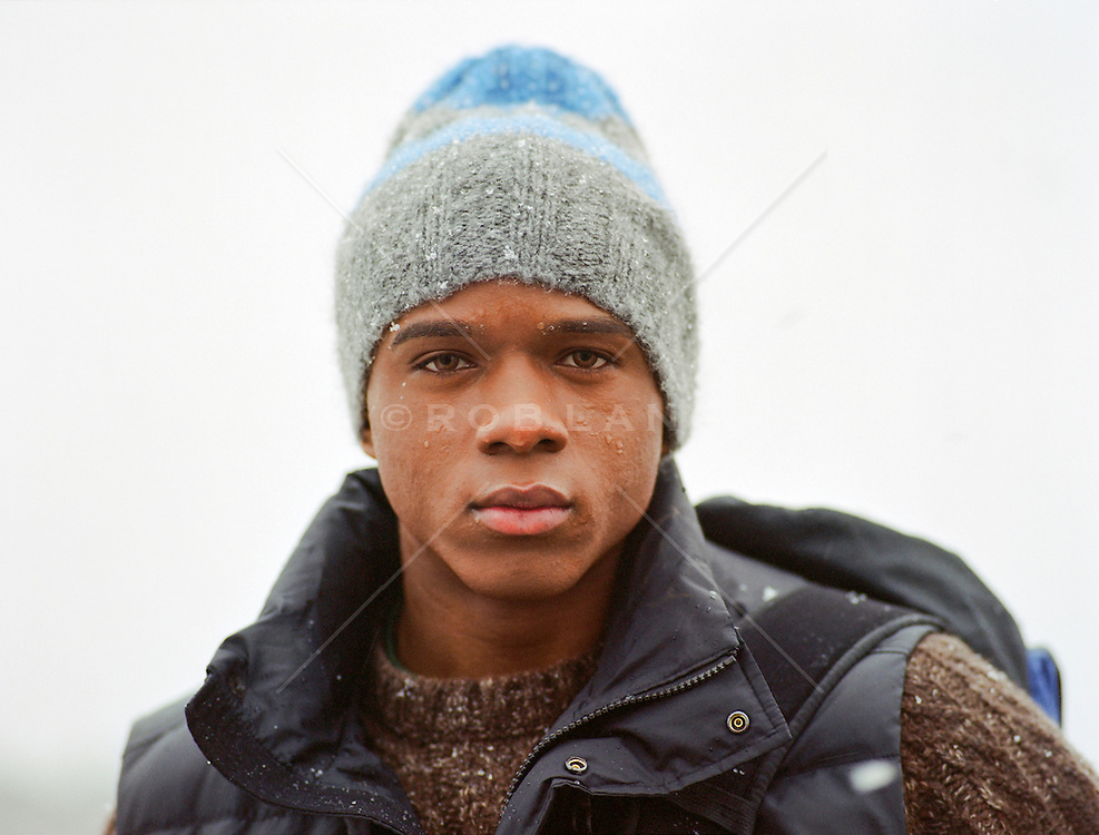 head and shoulders portrait of a young African American man with green eyes in the snow