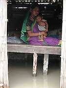 Bewilder flood victim an unidentified village woman sits on a high place, under their submerged house by floodwater and holds her only son at Motir village, about 313 kilometers southwest of Gauhati, the capital city of Northeastern Indian state, Assam, Monday, June 28, 2004. ..Floodwaters of the Asia'a one of the largest river, Brahmaputra and its 35 tributaries have affected more than one million in all of Indian subcontinent and disrupted communication in many parts of the India and Bangladesh, sources said.  (AP Photo/ Shib Shankar Chatterjee)