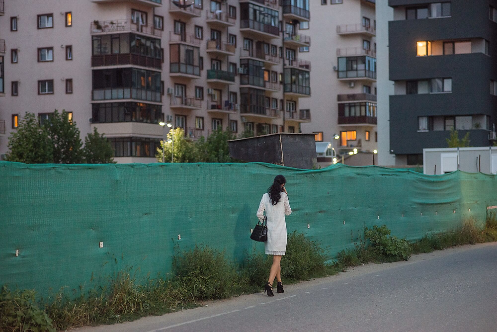 A woman walks past a newly built residential apartment block.