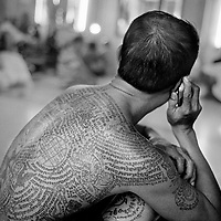 Nakhon Chai Si district, February 2010, Wat Bang Phra Temple. Religious tattoo on the back of a Thai pious Bouddhist, in Nakhon Chai Si district, Thailand, about 50 km west of Bangkok. The temple is famous for its monks and their practice of giving Sak Yant tattoos with wooden bamboo and metal needless. Many believe that protective energy flows through the tattoos, keeping them safe from harm. It is not simply about getting a talisman tattoo here. The owner must activate it in order for it to serve as a lifesaving conduit. He or she must respect the precepts set by the head master.