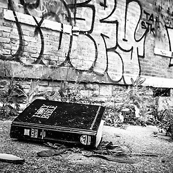 """Loss of Faith - Photo of a disacarded Holy Bible laying on the sidewalk among the ruins and graffiti of Cincinnati's Glencoe-Auburn Place. Known as """"The Hole"""" the complex was abandoned and in very poor condition.  The Glencoe-Auburn Place Row Houses were built in the late 1800's and were listed on the U.S. National Register of Historic Places. Glencoe-Auburn Place was demolished in March 2013."""