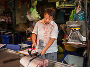 13 MAY 2015 - SAMUT SONGKRAM, SAMUT SONGKRAM, THAILAND:   A fish monger cuts up a fish for a customer in the market in Samut Songkram.    PHOTO BY JACK KURTZ