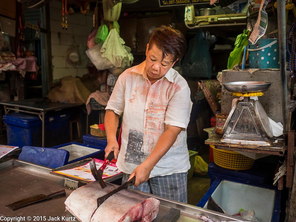 13 MAY 2015 - SAMUT SONGKRAM, SAMUT SONGKRAM, THAILAND:   A fish monger cuts up a fish for a customer in the market in Samut Songkram.    PHOTO BY JACK KURTZ