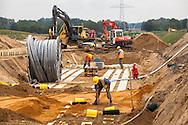 Europa, Deutschland, Nordrhein-Westfalen, Raesfeld, Baustelle des Netzbetreibers Amprion, der hier die bundesweit erste 380 kV-Hochspannungsleitung im Erdreich verlegt. Das Pilotprojekt, bei dem auch die Auswirkungen des magnetischen Feldes des Hochspannungsstroms auf den Pflanzenwuchs untersucht werden sollen, wird drei Kilometer lang sein und stellt einen von drei geplanten Testabschnitte auf der 130 Kilometer langen Trasse zwischen Meppen und Wesel dar. Die unterirdischen Kabel gelten als Alternative beim Bau neuer Stromtrassen, sind aber teurer als Strommasten und Ueberlandleitungen. - <br /> <br /> Europe, Germany, North Rhine-Westphalia, Raesfeld, construction site of the network operator Amprion, who installed the nation's first underground 380 kV high-voltage line.  It is a pilot project in which the effects of the magnetic field of high voltage current on plant growth will be tested. It will be three kilometers long and is one of three test sections of the 130 km-long route between Meppen and Wesel. The underground cables are considered to be an alternative for the construction of new power lines, but are more expensive than electricity pylons and overland lines.