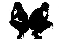 one sad caucasian couple man and woman crouching back to back in studio silhouette isolated on white background