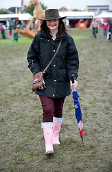 © Licensed to London News Pictures. 10/07/2012..Harrogate, England...Nicola Swines, 34 from Harrogate is dressed for the occasion during a muddy and wet opening day at the Great Yorkshire Show...England's premier agricultural show opened it's gates today for the start of three days of showcasing the best in British farming and the countryside...The event, which attracts over 130,000 visitors each year is the 154th show and displays the cream of the country's livestock and offers numerous displays and events and gives the chance to see many different countryside activities...Photo credit : Ian Forsyth/LNP
