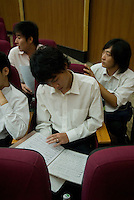 Young Chinese opera singer reviews his piece for his coming audition, Guangzhou, China.