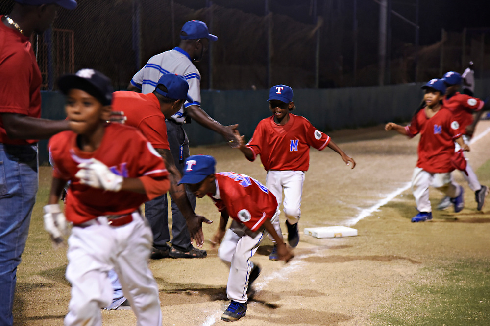 WILLEMSTAD, CURACAO - DECEMBER 10, 2014: Marchena Hardware players get high fives from their coaches after defeating team Trai Seru 12-3 during a tournament at the Frank Curiel field. The team wears Texas Rangers hats because Rangers player Jurickson Profar's little brother Jurdrick Profar is on the team. (photo by Melissa Lyttle)