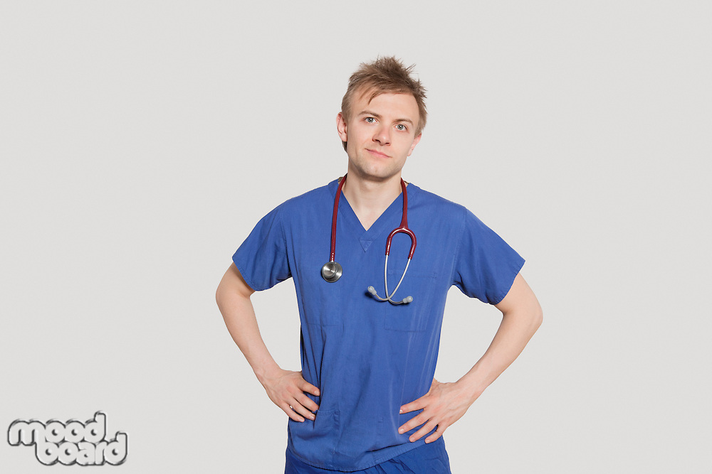 Portrait of male surgeon standing with hands on hips over gray background