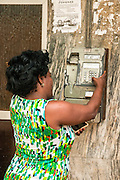 Cuba, Havana, woman uses a public pay phone while holding a cellphone in her hand