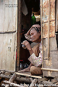 A woman who is a resident of a squatter's village sits in her home in Kampong Cham, Cambodia.  She is among 250 people who were displaced to this location from their former homes on the banks of the Mekong, River. The move was triggered by the construction of a large new hotel on the site of their former homes.  In all, thirty-nine families made the move and each received 50 kilograms of rice and plastic sheeting to wrap up their homes from the new hotel's owner.