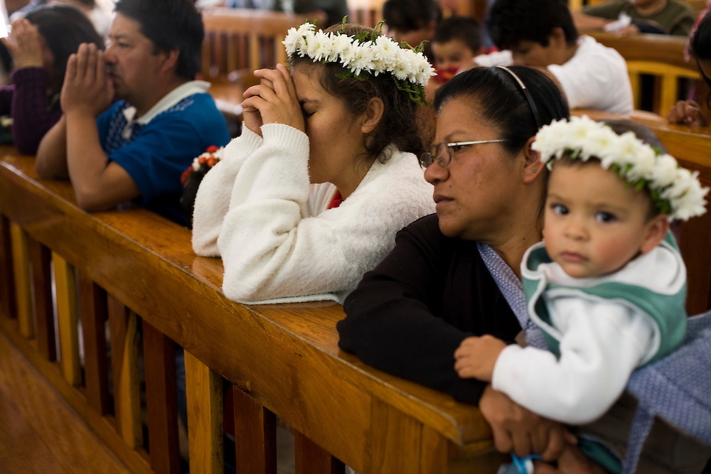 A family prays during mass at the church in Chalma.  Chalma is the second most important pilgrimage site in Mexico.  People come from all over the country to visit the Senor de Chalma. They often arrive wearing crowns made of flowers, and leave the crowns at the church.