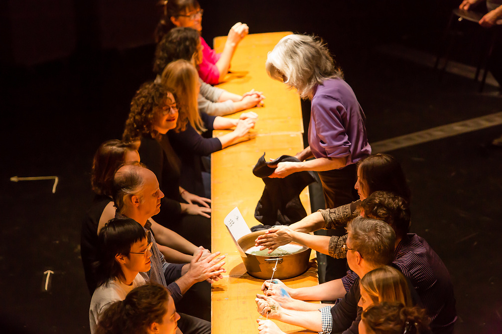 Brooklyn, NY - 11 December 2019. A performance of In Many Hands in BAM's Fishman Space, by Kate McIntosh in collaboration with Arantxa Martinez and Josh Rutter; sound design by John Avery; lighting design by Joëlle Reyms. The piece involves participants sitting at 3 long, narrow tables, with facilitators at each end, and either passing along objects or repeating hand movements in the manner set by a facilitator.  At this point, the table covering is rolled up, and participants wash their hands one at a time.