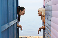 Two women leaning on beach house verandahs side view