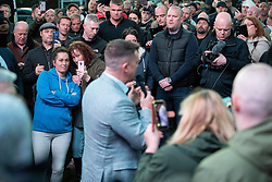 © Licensed to London News Pictures . 25/04/2019. Manchester, UK. Crowds listen as STEPHEN YAXLEY-LENNON (aka Tommy Robinson ) announces he is running for a seat in the European Parliament in North West England at a barbecue event on a green on a housing estate in Wythenshawe , South Manchester . Photo credit: Joel Goodman/LNP