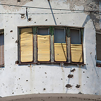 MOSTAR, BOSNIA AND HERZEGOVINA - JUNE 28:  A window and a concrete wall damaged by bulletts from the 1993 war is seen on June 28, 2013 in Mostar, Bosnia and Herzegovina. The Siege of Mostar reached its peak and more cruent time during 1993. Initially, it involved the Croatian Defence Council (HVO) and the 4th Corps of the ARBiH fighting against the Yugoslav People's Army (JNA) later Croats and Muslim Bosnian began to fight amongst each other, it ended with Bosnia and Herzegovina declaring independence from Yugoslavia.  (Photo by Marco Secchi/Getty Images)