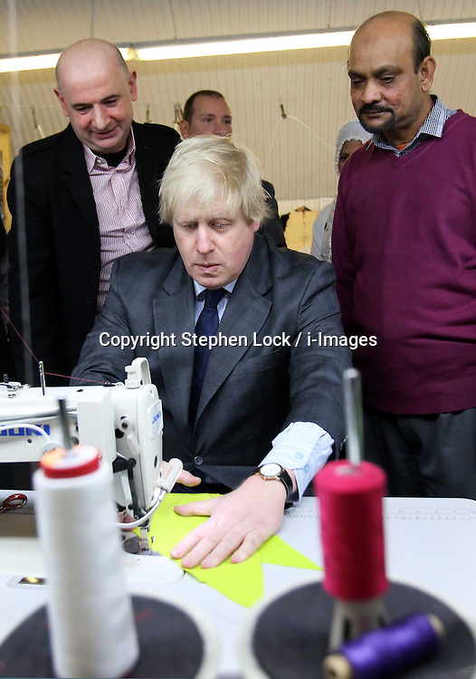 Boris Johnson, Mayor of  London, has a go on a sewing machine during a visit to  a new clothing factory in the East End of London, Tuesday, 26th February 2013. Photo by: Stephen Lock / i-Images