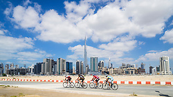 Cyclists on cycle track with skyline of Dubai in United Arab Emirates