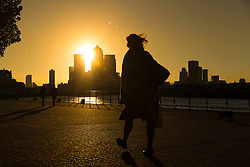 © Licensed to London News Pictures. 05/10/2016. LONDON, UK.  A woman walks on the River Thames path as the sun rises behind Canary Wharf and London's financial district this morning. Forecasters are predicting a day of clear and sunny weather in London today.  Photo credit: Vickie Flores/LNP