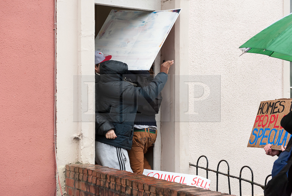 "© Licensed to London News Pictures.09/04/2016. Bristol, UK.  Protesters stop the door being closed by viewing agents and enter a property to stop viewings of council houses for auction in City Road, St Pauls, Bristol. Campaigners want the council to stop selling off 15 council homes on 20 April by auction to the private sector. Bristol City Council says the homes are expensive to repair, but some campaigners question whether the costs of repairs are inflated, and also whether the homes will be bought and then relet to the Council for temporary accommodation at higher than normal rents. Bristol resident Roger Yates said: ""The idea the Council can't afford to do these places up is piffle. All over Bristol folk are improving property to increase its value on a rising housing market. These are valuable assets. But Ferguson (Bristol's elected mayor) wants to socially cleanse inner city Bristol so that his luvvie mates can move in. The poor will relocate to Hartcliffe or the street."" A group of residents of St. Paul's and the Inner City are working together to put pressure on BCC to stop the sale. They are working in partnership with The Community Rights Project, The Bristol People's Assembly, and members of the ACORN community union. Photo credit : Simon Chapman/LNP"