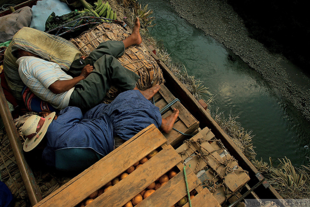 A Bolivian Aymara couple sleeps at the top of a truck carrying their tangerine crops aside the Coroico river valley near the village of Santa Rosa, some 143  km north of Bolivian capital La Paz on Sunday, May 21, 2006.Many families of this mountainous, subtropical region grow coca and fruits using creativity where government fails to provide necessary infraestructure to economic growth. (Dado Galdieri)