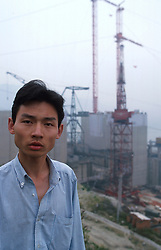 CHINA HUBEI PROVINCE THREE GORGES DAM MAY99 - A Chinese construction worker stands in front of the site of the Three Gorges Dam. Seven large cities, including Chongquing, and thousands of villages will be submerged once the water level rises after the completion of the controversial Three Gorges Dam project further downriver. The flooding of areas reaching back more than 550Km upriver will require the evacuation and resettlement of more than 10 million people.  jre/Photo by Jiri Rezac. . © Jiri Rezac 1999. . Tel:   +44 (0) 7050 110 417. Email: info@jirirezac.com. Web:   www.jirirezac.com