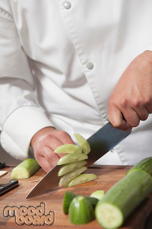 Mid- adult chef slicing cucumber