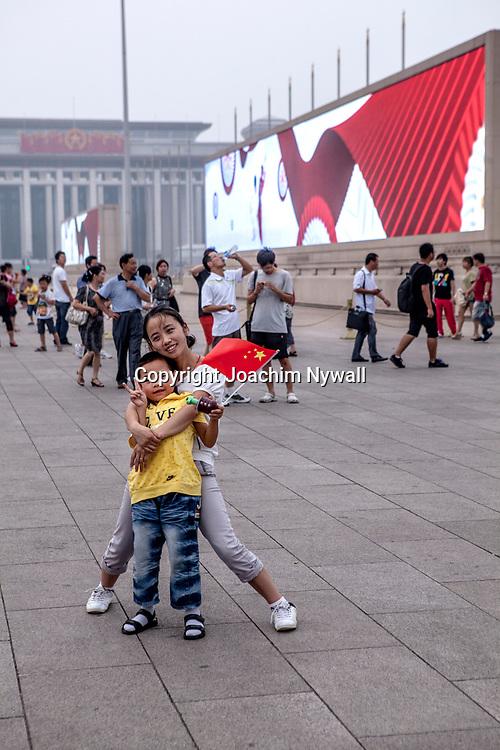 2011 08 Beijing Kina China<br /> Himmelska fridens torg &auml;r v&auml;rldens st&ouml;rsta torg, bel&auml;get i centrala Peking utanf&ouml;r Himmelska fridens port som leder till den F&ouml;rbjudna staden. Torget m&auml;ter ca 765x285 meter eller 220 000 m&sup2;<br /> Liten kille och tjej med kinesiska flaggan<br /> <br /> ----<br /> FOTO : JOACHIM NYWALL KOD 0708840825_1<br /> COPYRIGHT JOACHIM NYWALL<br /> <br /> ***BETALBILD***<br /> Redovisas till <br /> NYWALL MEDIA AB<br /> Strandgatan 30<br /> 461 31 Trollh&auml;ttan<br /> Prislista enl BLF , om inget annat avtalas.