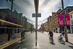 Glasgow, Scotland, UK. 12 June 2020.  Although shops can reopen in England next week, in Scotland the lockdown is not being relaxed so quickly with several more weeks of restrictions to go. Shops and businesses remain closed and streets are very quiet. Pictured; Buchanan Street shopping precinct reflected in shop window.  Iain Masterton/Alamy Live News