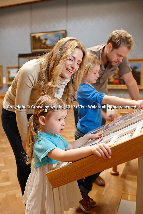 Family looking at interactive display in art gallery<br /> National Museum<br /> Cardiff<br /> South<br /> Children<br /> Families<br /> Lifestyle<br /> Tourist Attractions