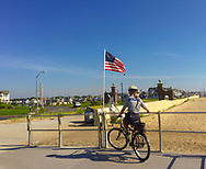 Spring Lake, NJ -- July 16, 2018. A police woman patrols the Spring Lake boardwalk on bicycle