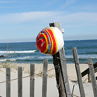 Lost bicycle helmet on sand dune fence post, Lavalette, New Jersey