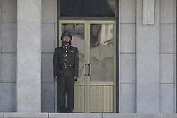 April 18, 2018 - Paju, GYEONGGI, SOUTH KOREA - April 18, 2018-Pamunjom, South Korea-North Korean security guard stand watch to south area visitors before the military demarcation line during a press tour to the border truce village of Panmunjom in the Demilitarized Zone (DMZ) dividing the two Koreas. North Korean leader Kim Jong Un and South Korean President Moon Jae-in are due to meet on April 27 at the South's side of the demilitarized zone for the landmark inter-Korean summit. (Credit Image: © Ryu Seung-Il via ZUMA Wire)