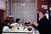 Peter Menzel has a meal with the Ukita children in their Kodaira City home during the week he spent with them to shoot the family for the Material World book. Japan. Material World Project. The Ukita family lives in a 1421 square foot wooden frame house in a suburb northwest of Tokyo called Kodaira City.