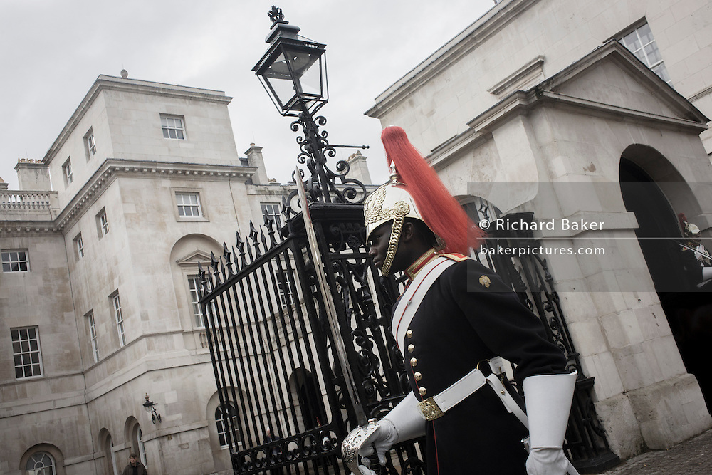 A black mounted lifeguard trooper parades at Horseguards in Whitehall, Westminster, Central London. <br /> This regiment is classed as a corps in its own right, and consists of two regiments: Life Guards (British Army) and the Blues and Royals (Royal Horse Guards and 1st Dragoons). They are the senior regular regiments in the British Army, with traditions dating from 1660. (Desaturated version). (Desaturated version).
